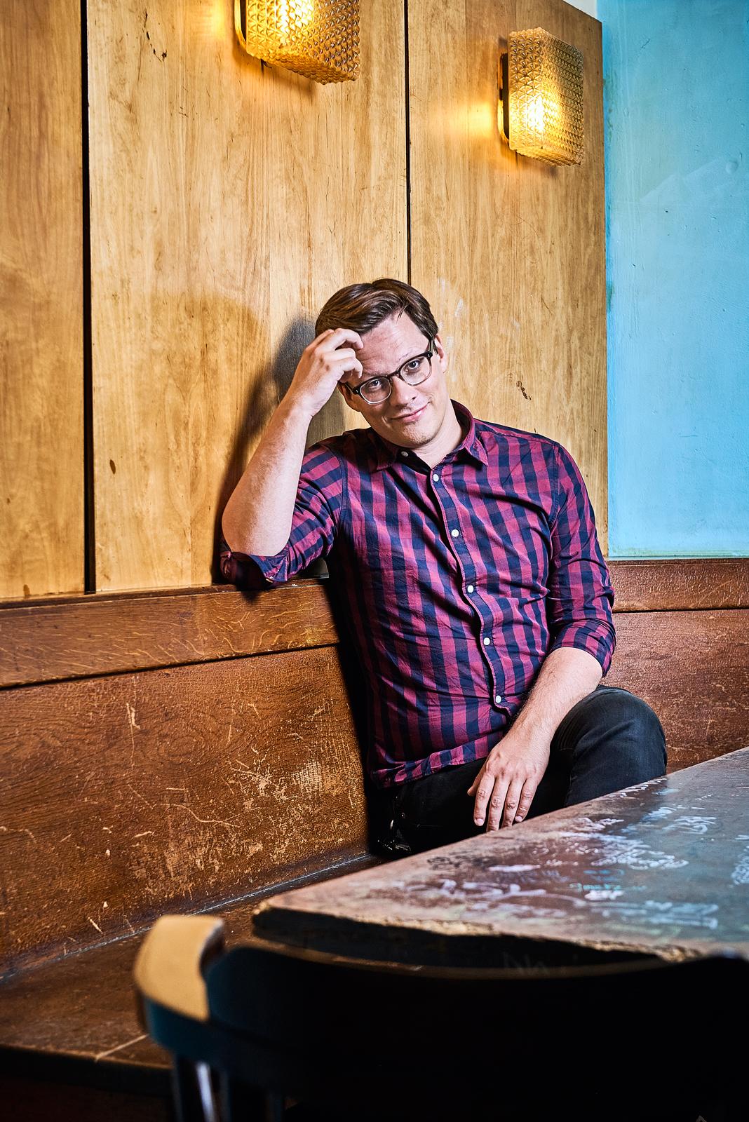Das Bild zeigt Martin Hommel. Er sitzt in einer Kneipe und schaut in die Kamera. Er lächelt.